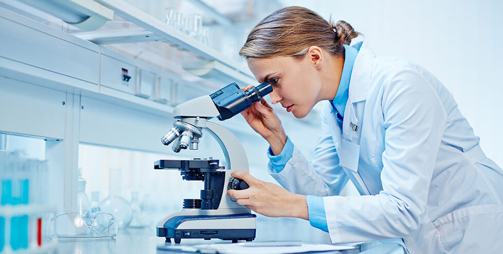 Photo of a researcher looking into a microscope
